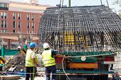 Steel rebars for reinforced concrete. Construction worker unload from the truck a part of einforcement steel prefabrication a steel reinforcements for bridge renovation with the help of a construction crane. Reinforcement steel for bridges. poster