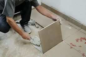 Gluing Tiles On The Wall. Laying Tiles On The Wall.  Worker Installing Big Ceramic Tiles On The Wall