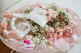 Wedding Gold Rings On Traditional White Pillow With Pink Ribbon Ready For Wedding Ceremony