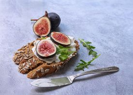 Closeup Of Healthy Open Sandwich With Cream Cheese And Figs Over Dark Bread With Sunflower Seeds On
