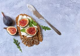 Top View Of Healthy Open Sandwich With Cream Cheese And Figs Over Dark Bread With Sunflower Seeds On