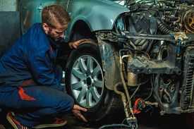 Serviceman Checking Suspension In A Car At Garage. Mechanic Repaired Wheeled Vehicles. Mechanic Hold