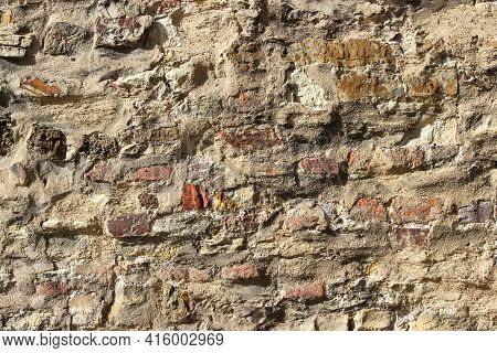 Texture Of An Old Damaged Brick Wall Coated With Heavily Damaged Plaster