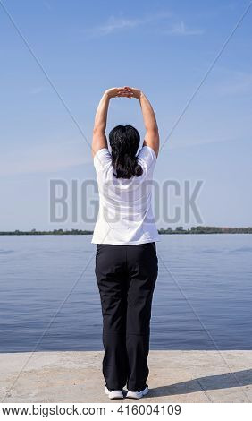 Active And Happy Senior Woman Exercising Near The Riverside