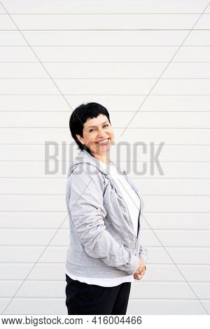 Senior Woman Waring Gray Jacket Standing Outdoors On Gray Solid Background