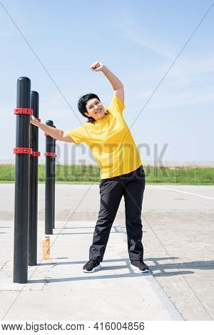 Senior Woman Stretching Her Back Outdoors On The Sports Ground