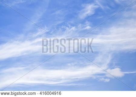 White Cirrus Rising Clouds Against Blue Sky. Atmospheric Phenomenon. Natural Background. Copy Space.