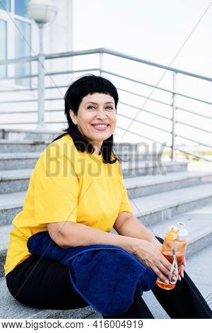 Senior Woman Drinking Water After Workout Outdoors On Urban Background