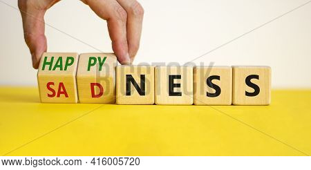 Happyness Or Sadness Symbol. Businessman Turns Cubes And Changes The Word 'sadness' To 'happyness'.