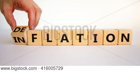 Inflation Or Deflation Symbol. Businessman Turns Cubes And Changes The Word Inflation To Deflation.