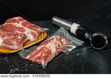 Meat In Bags And Sous Vide Devices On A Black Background.