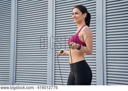 Smiling Pretty Holding Skipping Rope And Going To Jump