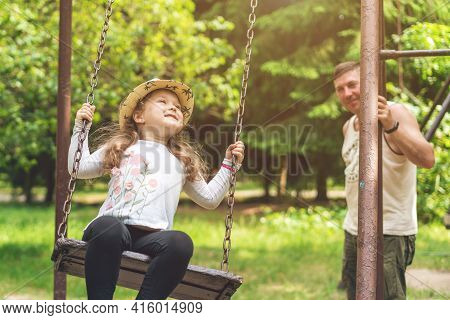 Dad Swings His Little Happy Daughter On A Swing On A Warm Sunny Day.
