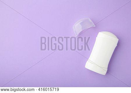 White Antiperspirant Deodorant On Purple Background. Skin Care Concept. Copy Space