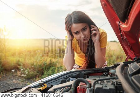 Car Breakdown. A Young Woman Calls On The Phone While Standing By A Broken Car With An Open Hood.