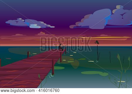 A Fisherman Sits In The Night On Pier And Fishes In The Lake. A Beautiful Sunset Over The Sea. The S