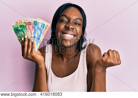 Young african american woman holding south african rand banknotes screaming proud, celebrating victory and success very excited with raised arm