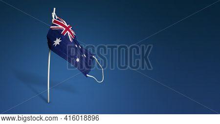 Australia Mask On Dark Blue Background. Waving Flag Of Australia Painted On Medical Mask On Pole. Co