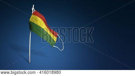 Bolivia Mask On Dark Blue Background. Waving Flag Of Bolivia Painted On Medical Mask On Pole. Concep