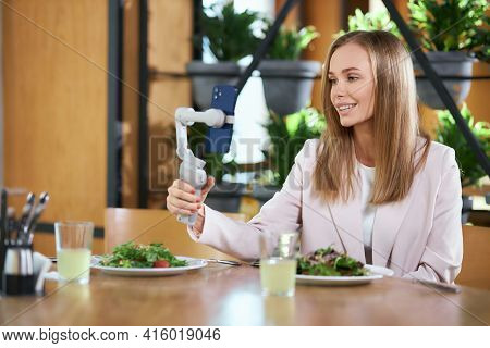 Side View Of Happy Beautiful Young Blogger Woman Holding Selfie Stick With Modern Phone And Doing Se