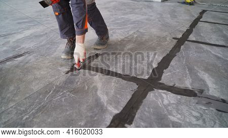 Black Grout Tiles On The Floor. Close-up Of A Professional Cleaner Cleaning The Grout With A Brush O