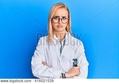 Beautiful caucasian oculist woman wearing robe and optometry glasses skeptic and nervous, disapproving expression on face with crossed arms. negative person.