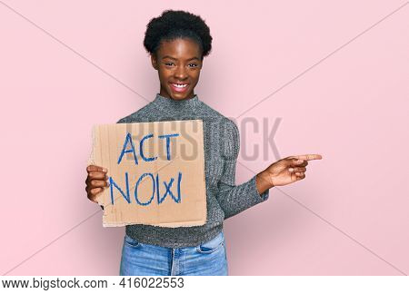 Young african american girl holding act now banner smiling happy pointing with hand and finger to the side