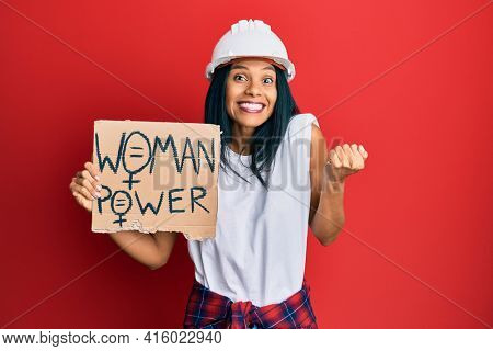 Young african american woman wearing architect hardhat holding woman power banner screaming proud, celebrating victory and success very excited with raised arm