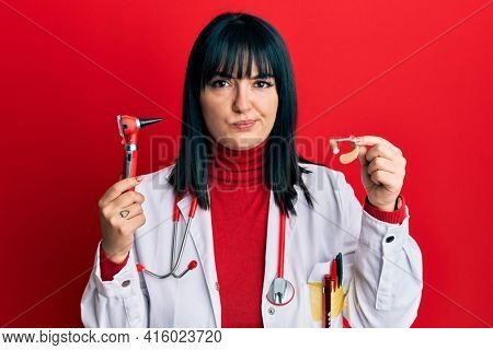 Young hispanic doctor woman holding deafness headset and otoscope skeptic and nervous, frowning upset because of problem. negative person.