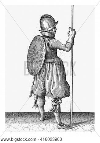 The exercise with shield and spear: the soldier standing with the spear resting on the ground next to the right foot, vintage engraving.
