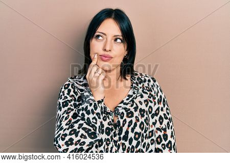 Young hispanic woman wearing casual clothes thinking concentrated about doubt with finger on chin and looking up wondering