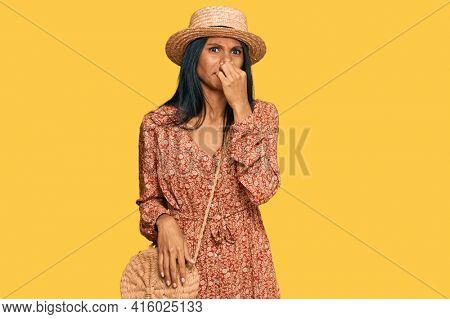 Young african american woman wearing summer hat smelling something stinky and disgusting, intolerable smell, holding breath with fingers on nose. bad smell