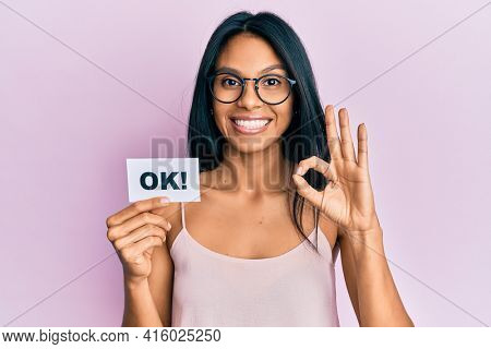 Young african american woman holding ok message paper doing ok sign with fingers, smiling friendly gesturing excellent symbol