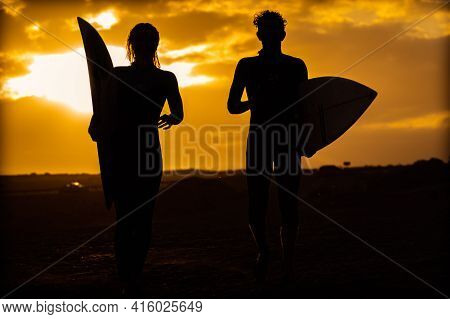 Silhouette Young Couple Surfers Stay On The Sunset Beach. Surfers Walking With Surfboards To The Bea