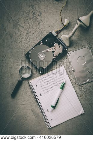 Concept of data recovery, reading data from corrupted hard drive. Hdd disk restoration, magnifier and binary code