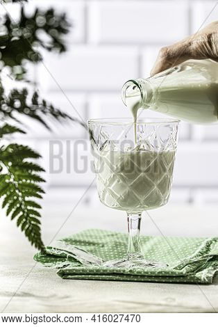 Kefir Are Poured Into A Glass Cup From A Bottle. Fermented Drink Kefir, Yogurt In A Glass Jar On A L
