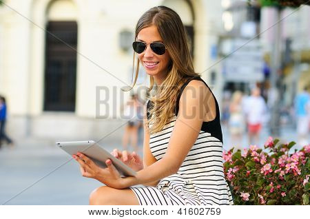 Attractive Blonde Woman With Tablet Computer In Urban Background