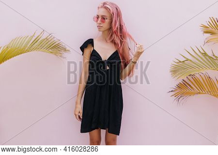 Tanned Fascinating Girl In Black Attire Posing In Studio With Palm Trees. Indoor Photo Of Thoughtful