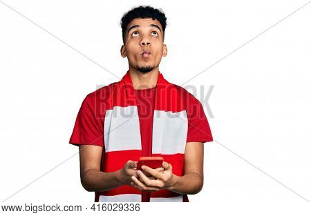 Young african american man football hooligan cheering game holding smartphone making fish face with mouth and squinting eyes, crazy and comical.