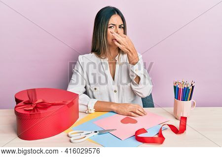 Young hispanic woman making valentine gift sitting on the table smelling something stinky and disgusting, intolerable smell, holding breath with fingers on nose. bad smell