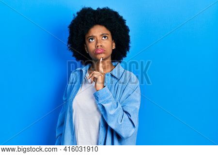 Young african american woman wearing casual clothes thinking concentrated about doubt with finger on chin and looking up wondering