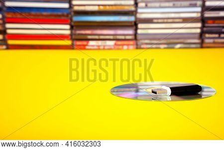 A Usb Flash Drive With Cd On The Background Of Cds On A Yellow Table.