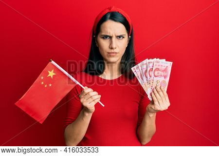 Young hispanic woman holding china flag and yuan banknotes skeptic and nervous, frowning upset because of problem. negative person.