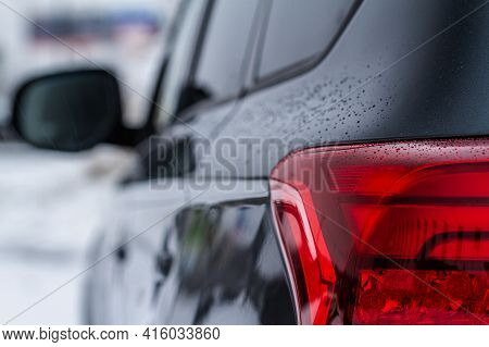 Close Up Detail On One Of The Taillight Of Modern Dark Car. Exterior Closeup Detail. Closeup Stoplig