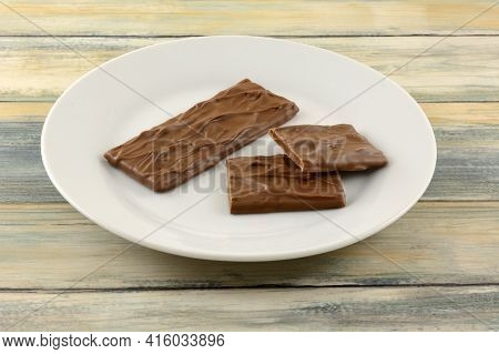 Candy Bar Of Almond Caramel Covered In Rich Milk Chocolate And Pieces On White Snack Plate