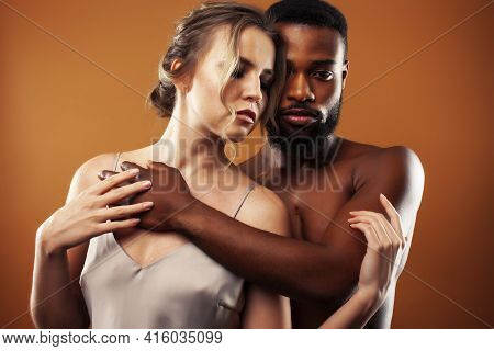 Young Pretty Couple Diverse Races Together Posing Sensitive On Brown Background, Lifestyle People Co