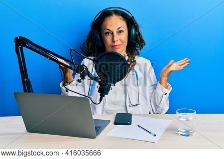 Beautiful middle age doctor woman working at radio studio clueless and confused expression with arms and hands raised. doubt concept.