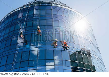 Four Industrial Climbers Clean Windows Outside A Circular Business Center With Mirrored Windows. The