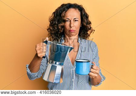 Middle age hispanic woman drinking italian coffee skeptic and nervous, frowning upset because of problem. negative person.