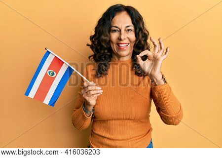 Middle age hispanic woman holding costa rica flag doing ok sign with fingers, smiling friendly gesturing excellent symbol